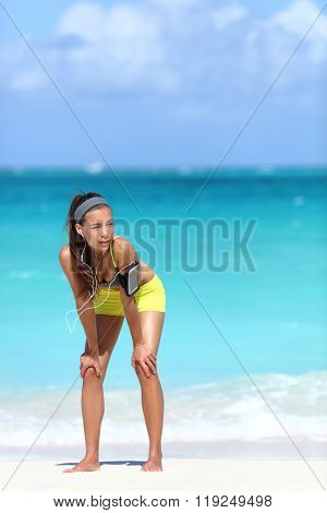 Running fitness woman exhausted after run on beach. Asian runner tired resting hands on knees thinking getting ready before exercising. Focus or motivation concept for workout.