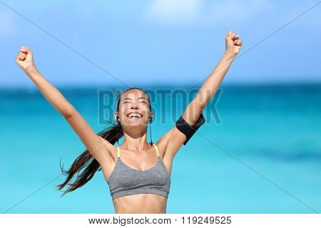 Happy running woman winning - fitness goal concept. Young Asian female runner smiling of happiness cheering with arms up wearing a sports bra, earphones and phone armband cheering of success.