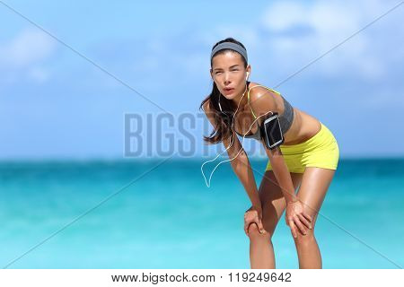 Tired runner breathing taking a run break on beach with ocean background. Asian chinese athlete woman resting hands on knees exhausted taking a rest post workout catching a breath.