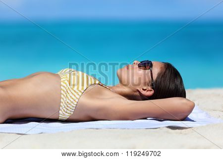 Beach sunglasses woman tanning relaxing in bikini. Sexy young adult wearing eyewear for sun protection lying down on towel on sand sunbathing closeup portrait. Skincare UV sun care concept.