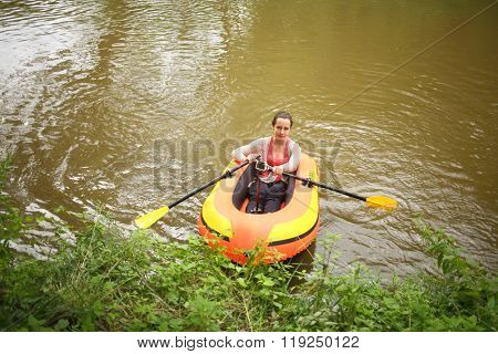 Woman with oars and action camera in a rubber boat near the shore, top view