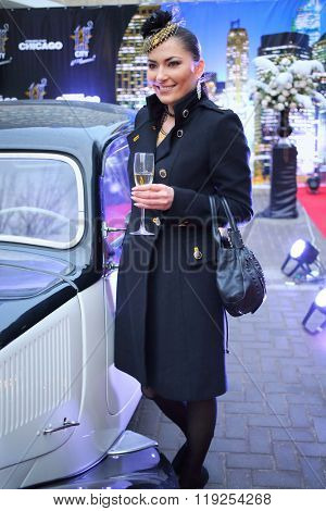 MOSCOW - APR 26, 2015: Beautiful woman near retro car at a party in honor of the birthday the glossy magazine LF city in karaoke club Chicago