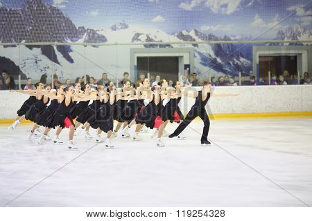 MOSCOW - APR 26, 2015: The team of girls in black costumes with a boy performs on the skate at the Cup in synchronized figure skating in the sports complex Olympiysky