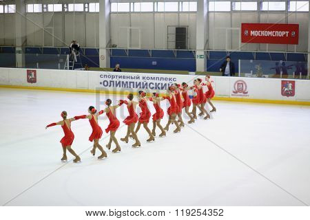 MOSCOW - APR 26, 2015: The team of girls in red costumes performs on the skate at the Cup in synchronized figure skating in the sports complex Olympiysky
