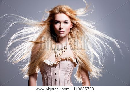 Portrait of the beautiful sexy woman with long blonde hair. Fashion model posing in the studio on a black background with flying hair.