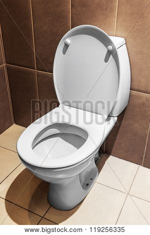 white ceramic toilet in tiled bathroom. Focus on the edge of the toilet bowl