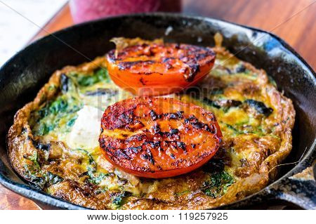 Omelette with tomato and greens on cast iron frying pan. Rustic breakfast omelette with grilled tomato and herbs. Selective focus shallow dof