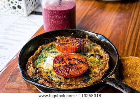 Omelette with tomato and greens on cast iron frying pan. Rustic breakfast omelette with grilled tomato and herbs and berry smoothie. Selective focus shallow dof
