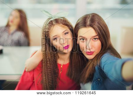 Two girls pouting while taking a selfie photo on mobile phone, selective focus