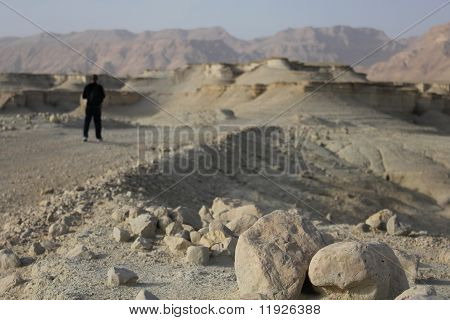 Pilgrim in the Judea Desert. Salt and rocks at Dead Sea, Israel