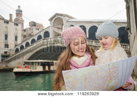 Mother And Daughter Looking In Map In Front Of Rialto Bridge