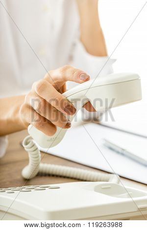 Female Hand Picking Or Hanging Up White Telephone Receiver
