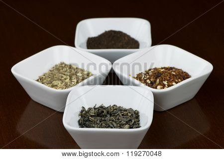 Dry tea leaves in square bowls with reflection