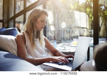 Charming European woman chatting in social network via net-book while sitting in modern interior