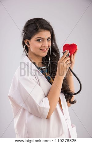 beautiful female indian doctor holding red heart