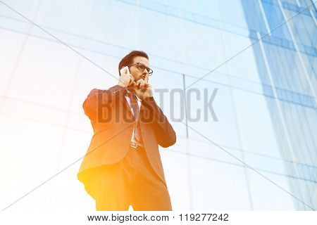 Businessman showing a sign of quiet during cell telephone conversation outside of skyscraper