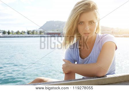 Attractive female with gorgeous blonde hair posing near sea to create a portfolio for model agency
