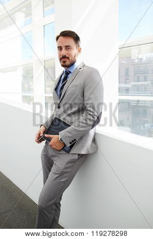 Male confident financier standing with mobile phone and touch pad in office interior