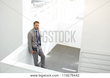 Male CEO standing with digital tablet in modern office interior during work break