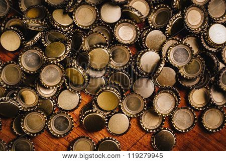 Large Pile Of Beer Bottle Caps On Wooden Desk