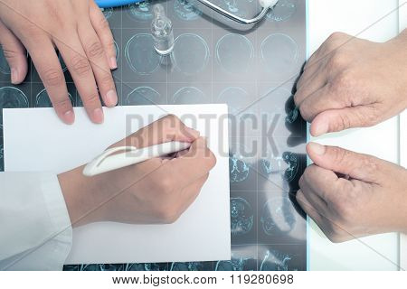 Doctor Writing Medical Opinion In Front Of Patient.