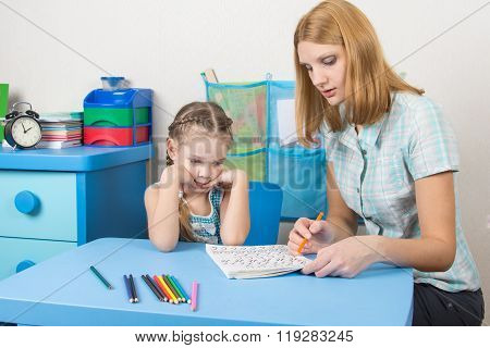 Five-year Girl With Interest Looks At The Teaching Material Explained By An Adult