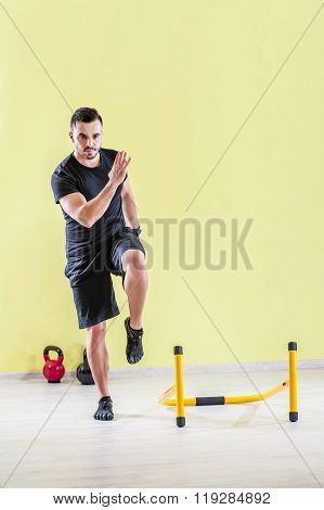 Young man at gym, exercising with handles