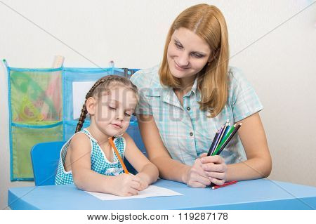 The Five-year Child Draws On A Sheet Of Paper, Next To The Teacher Holds Pencils
