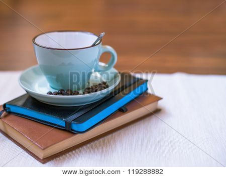 Cup of coffee with book and note-book. Morning calm concept