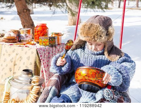 Little Boy In A Cap With Earflaps Plays Winter Park.  Russian Style On A Background Of Samovar And W