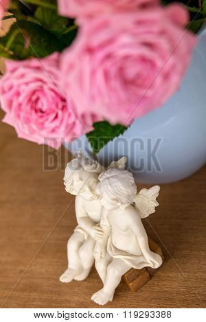 Pink flowers in blue jug. Roses in jug. Wooden background. Two angels on bench. Flowers in vase. Sha