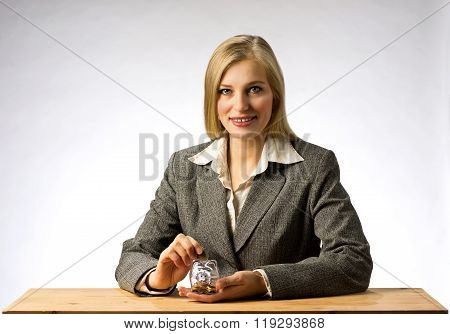 Businesswoman sitting at office table and holding money box. Business woman with gray jacket putting