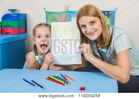 Five-year Girl And The Teacher Happily Show Drawn On A Sheet Of Wood