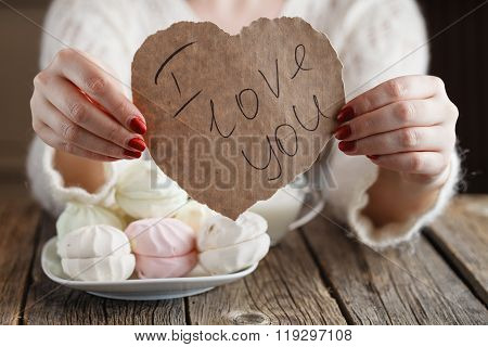 Woman Holding Paper Heart While Eating Sweets