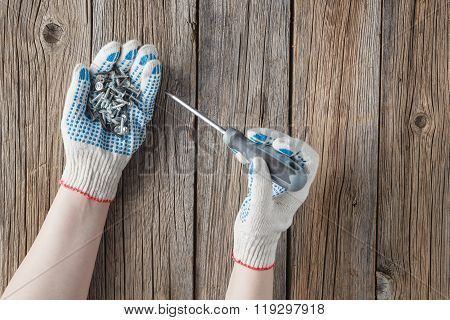 Hand Of The Worker Screws In A Wooden Block With A Screwdriver