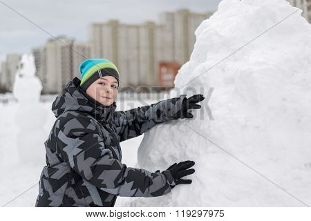 Teen Boy Standing At Makeshift Snow Fort
