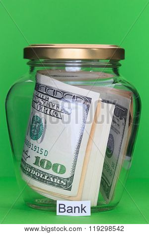 Money In Glass Jars, On Green Background With Sign – Bank