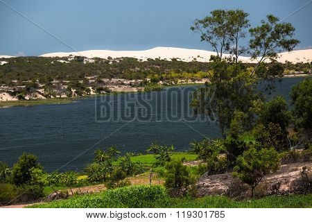 Lake with green coasts and trees in the desert. White sandy dunes on the horizon. Area of the town of Mui Ne, Vietnam