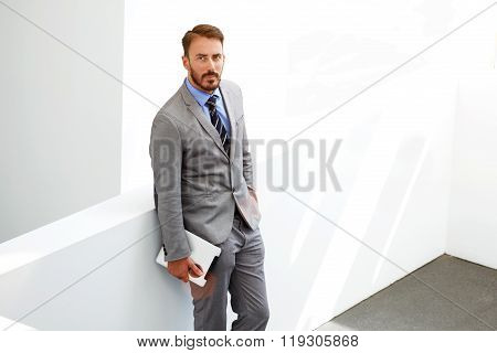 Confident manager standing with digital tablet near copy space
