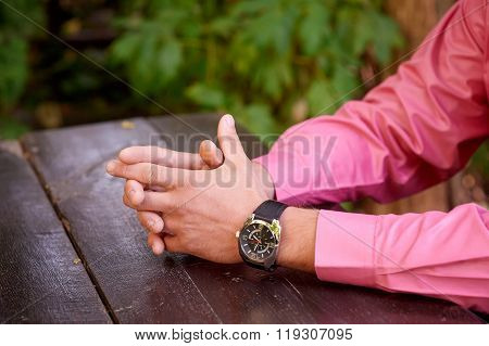 man with his hands clasped in front of him