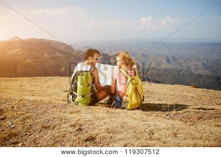 Cheerful happy tourists resting after walking in mountainous areas during summer adventure