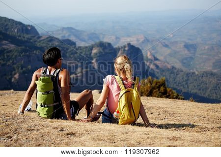Back view of a young man and woman enjoying amazing view while sitting on a high mountain