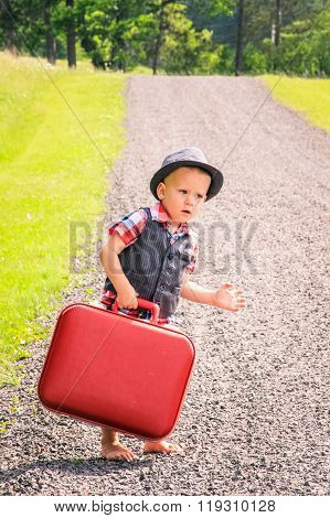 Little boy struggling to carry suitcase down rural road