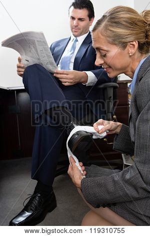Woman polishing businessmans shoe