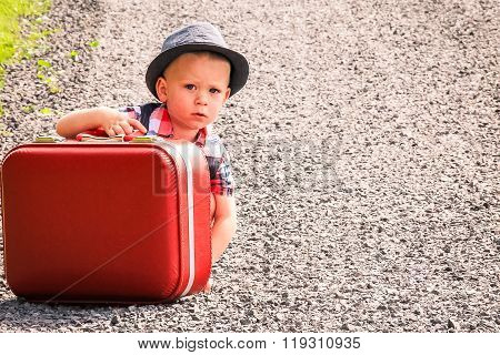 Little boy crouching on road with suitcase