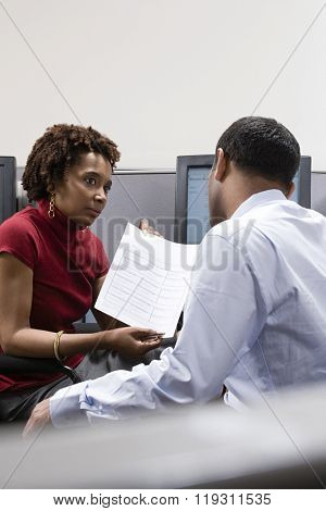 Woman showing form to colleague
