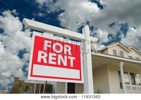 For Rent sign in front of new home. Dramatic Blue Sky and clouds behind.
