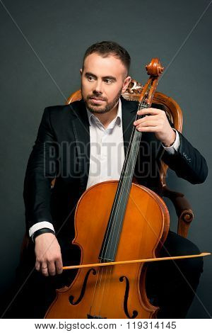 portrait of young man in black suit with cello