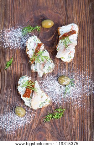 Herring sandwich with sun-dried tomatoes herbs basil and soft cream cheese. Sandwiches of buckwheat bread and herring. Pieces of fish are herring on bread. Fish dishes. Scandinavian cuisine.