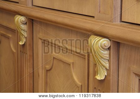 Decorative petals on the facade of a wooden bookcase, close-up